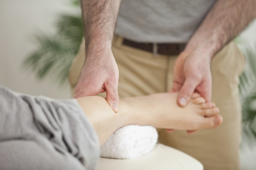 Close up of a man massaging a foot in a room